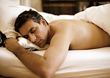 Man lying on stomach in bed, elbow out, eyes closed, waist up